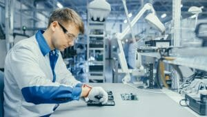 Young Man in Blue and White Work Coat is Using Plier to Assemble Printed Circuit Board for Smartphone. Electronics Factory Workers in a High Tech Factory Facility.